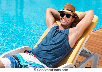 Positive handsome man resting near the pool