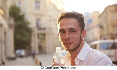 Positive handsome thirsty man in his 20s drinking water from...
