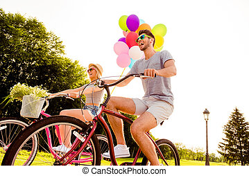 Positive happy man having date and riding bicycles with his girlfriend