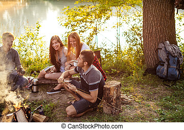 positive hikers sitting around the bonfire and looking at their friend