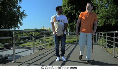 Positive hindu volunteer helping a senior man with a walking...