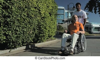 Positive hindu volunteer pushing a wheelchaired man