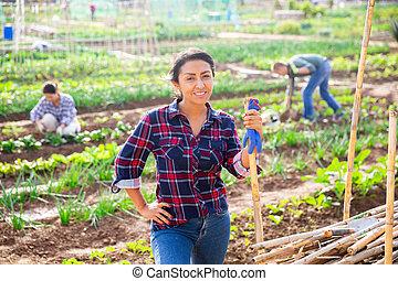Positive hispanic woman gardener posing in vegetable garden