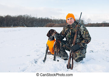 positive hunter with dogs during the rest on winter hunting