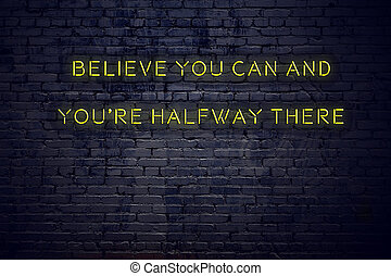 Positive inspiring quote on neon sign against brick wall believe you can and youre halfway there