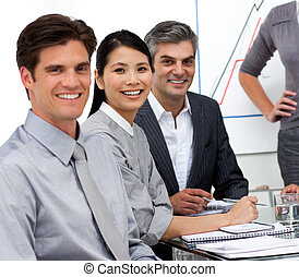 Positive international business people at a presentation looking at the camera