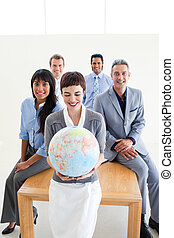 Positive international business people holding a terrestrial globe in the office