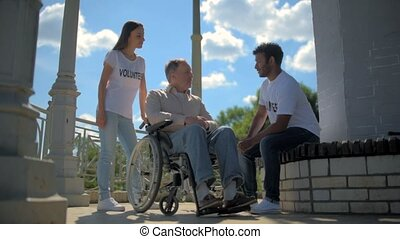 Positive international volunteers talking with a wheelchaired man
