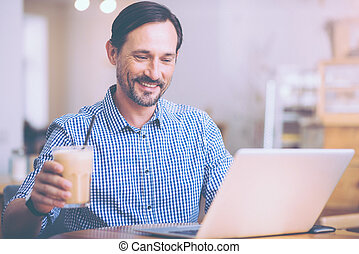 Positive involved man sitting in the cafe