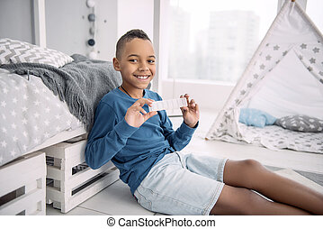 Positive jolly boy showing container for pills