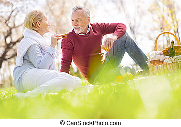 Positive joyful man having a picnic with his wife
