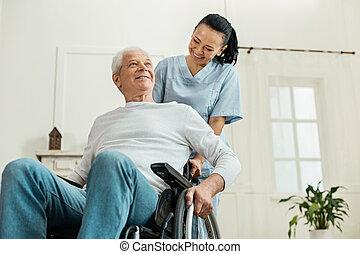 Positive joyful man sitting in the wheelchair