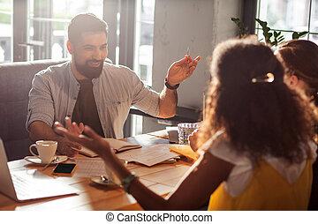 Positive joyful man speaking with his team