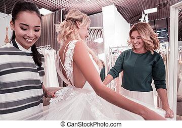 Positive joyful woman looking at her daughters dress -...