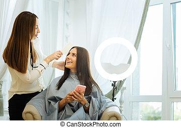 Positive joyful woman looking at her hair stylist