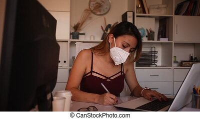 Positive latina woman in protective mask and casual wear working alone with laptop and papers in office