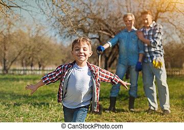 Positive little boy running in the garden