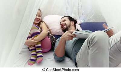 little girl and her father reading a book together