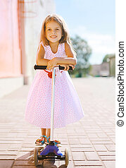 Positive little girl riding a scooter having fun