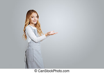 Positive little girl standing isolated on grey background