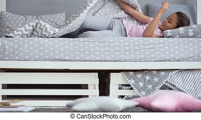 Positive little girl waking up from her bed