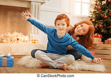 Positive little kid and his mom playing on Christmas morning