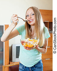 long-haired blonde girl eating fruit salad in home