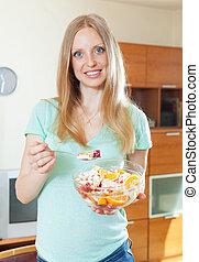 long-haired blonde girl eating fruit salad