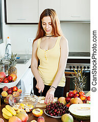 Positive long-haired woman cooking fruit salad