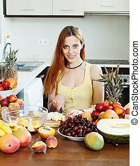 Positive long-haired woman making chopped fruit salad