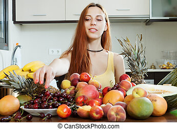long-haired woman with heap of ripe fruits