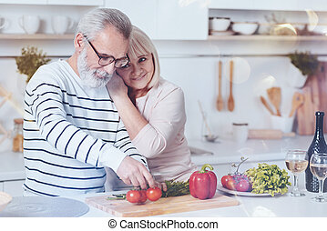 Positive lovign aged couple standing in the kitchen