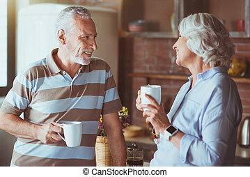 Positive loving couple drinking tea in the kitchen