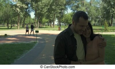 Positive loving couple having a nice walk in the park - My...