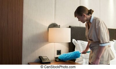 Positive maid cleaning dust on bedside cabinet - Scrub and...