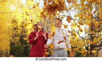 Positive man and woman throw dry yellow leaves in park - ...