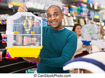 Positive man buying bird cage at store