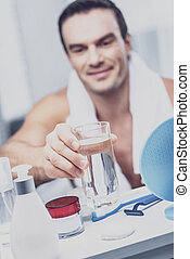 Positive man putting a glass of water on the shelf