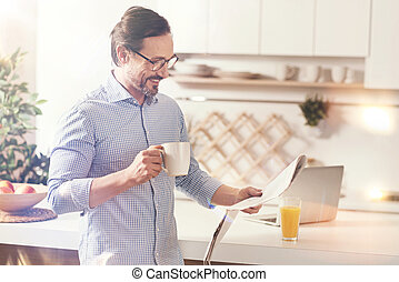Positive man reading newspaper in the kitchen