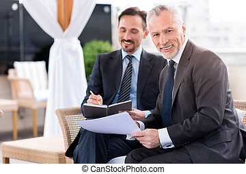 Positive man sitting with his colleague