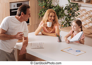Positive mature father enjoying weekend with family indoors