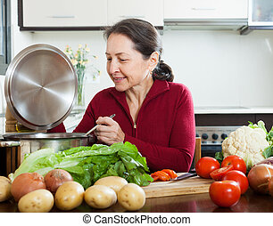 woman cooking with soup ladle in domestic kitchen - Positive...