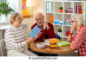 Positive mature woman reading a book to her friends