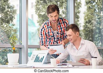 Positive men discussing project