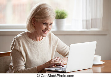Positive middle aged female sitting at table using notebook