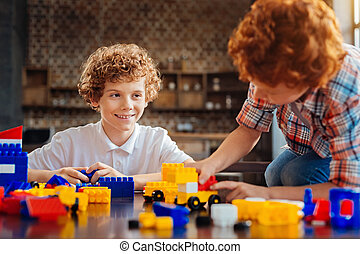 Positive minded brothers playing with lego together