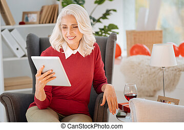 Positive minded elderly woman using tablet computer at home