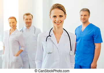 Positive minded female practitioner with stethoscope posing for camera