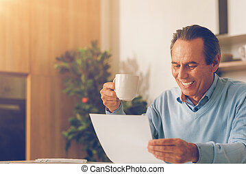 Positive minded mature businessman reading document at home
