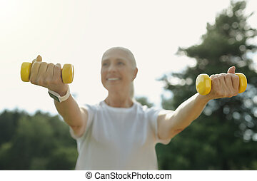 Positive minded retired woman training with weights